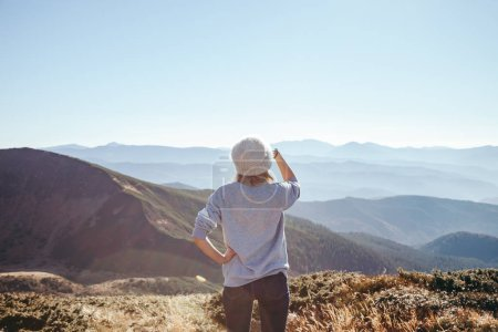 rear view of female explorer looking at scenic mountains on sunny day, Carpathians, Ukraine