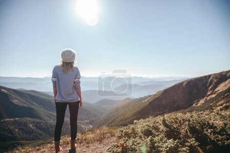 Photo for Rear view of female traveler looking at mountains on sunny day, Carpathians, Ukraine - Royalty Free Image