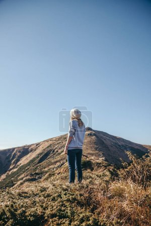 rear view of woman looking at beautiful mountains on sunny day, Carpathians, Ukraine