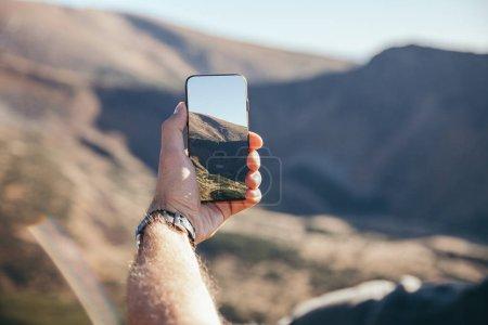 Photo pour Plan recadré de l'homme prenant des photos de montagne avec smartphone, Carpates, Ukraine - image libre de droit