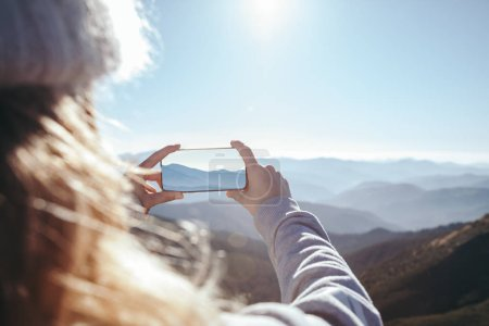cropped shot of woman taking photo of mountain with smartphone, Carpathians, Ukraine