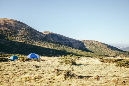 camping tents in beautiful mountains under blue sky, Carpathians, Ukraine