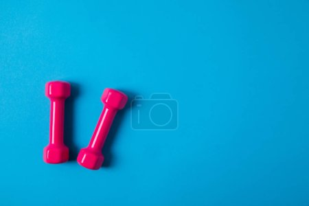 Photo for Flat lay with pink dumbbells isolated on blue, minimalistic concept - Royalty Free Image