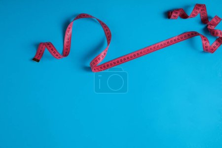 top view of pink measuring tape isolated on blue, minimalistic concept