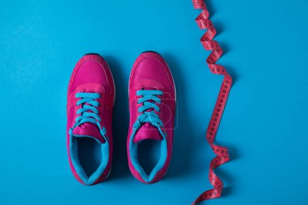 view from above of pink sport shoes and measuring tape isolated on blue, minimalistic concept