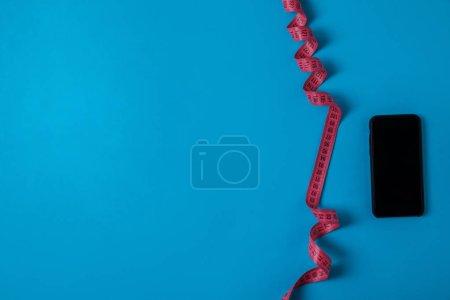 Foto de Vista superior de medición cinta y smartphone con pantalla en blanco aislada en concepto minimalista, azul rosa - Imagen libre de derechos