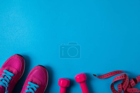 Photo for Elevated view of pink sneakers, dumbbells and measuring tape placed in row isolated on blue - Royalty Free Image
