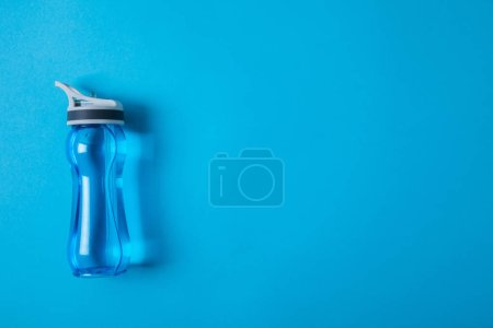 view from above of sport bottle with water isolated on blue, minimalistic concept