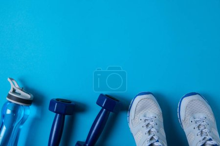 flat lay with sportive sneakers, dumbbells and sport bottle isolated on blue