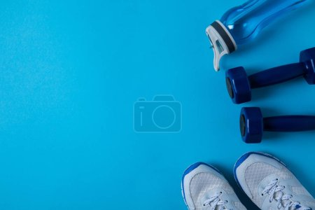 Photo for Elevated view of dumbbells, sneakers and sport bottle with water isolated on blue - Royalty Free Image