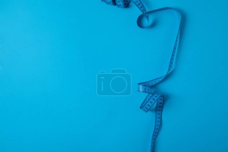 top view of measuring tape isolated on blue, minimalistic concept