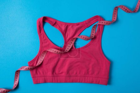 elevated view of pink sports bra and measuring tape isolated on blue, minimalistic concept