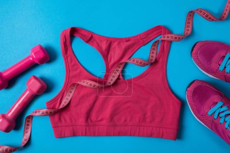 top view of pink dumbbells, measuring tape, sports bra and sneakers isolated on blue