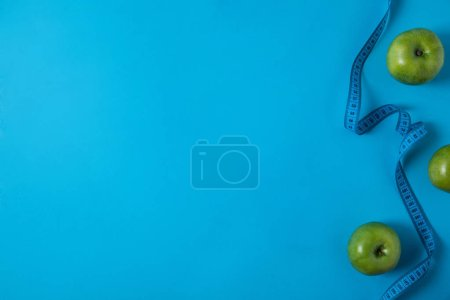 view from above of green apples and measuring tape isolated on blue