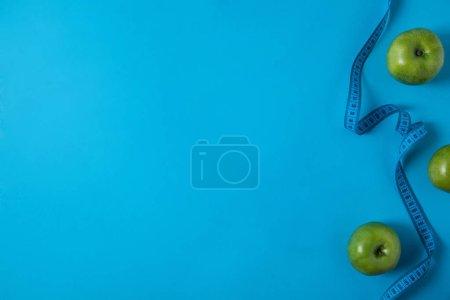 Foto de Vista desde arriba de las manzanas verdes y aislada en el azul de la cinta de medición - Imagen libre de derechos