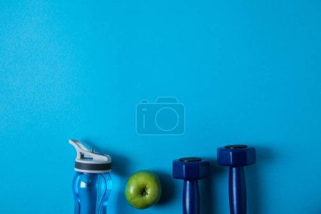 Photo for Elevated view of arranged sport bottle, green apple and dumbells isolated on blue, minimalistic concept - Royalty Free Image