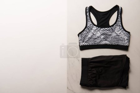 view from above of sports bra with shorts on marble and white, minimalistic concept