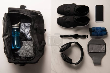 Photo for Flat lay with sports bag and arranged sports equipment on white and marble - Royalty Free Image