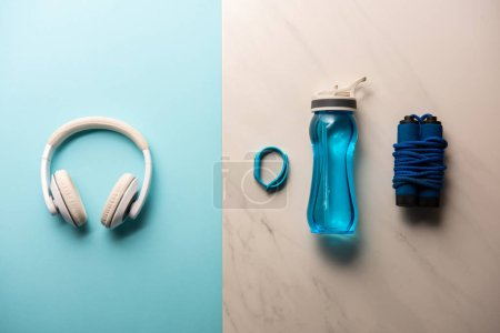 flat lay with headphones, bottle of water, jump rope and fitness tracker on blue and marble