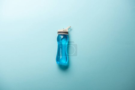 elevated view of sport bottle isolated on blue, minimalistic concept