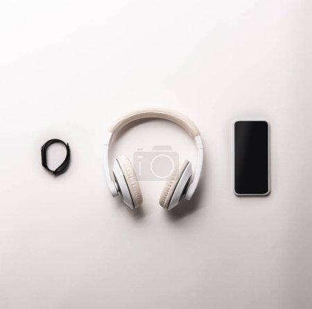Photo for Top view of fitness tracker, headphones and smartphone with blank screen placed in row isolated on white, minimalistic concept - Royalty Free Image