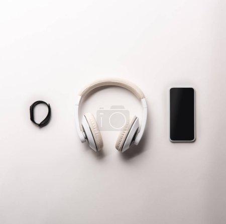 Foto de Vista superior de fitness tracker, auriculares y smartphone con pantalla en blanco colocado en fila aislado en blanco, minimalista concepto - Imagen libre de derechos