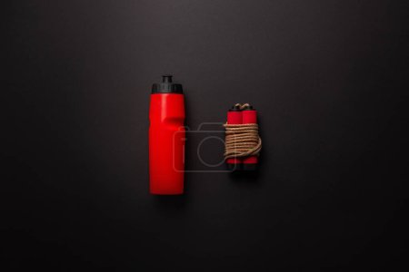 Photo for Flat lay with red sport bottle and jump rope isolated on black, minimalistic concept - Royalty Free Image