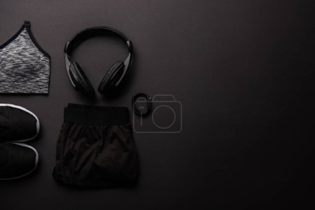 Photo for Top view of arranged sportswear, headphones and fitness tracker isolated on black - Royalty Free Image