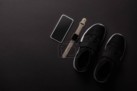 Photo for Top view of arranged smartphone, smartwatch and sneakers isolated on black, minimalistic concept - Royalty Free Image