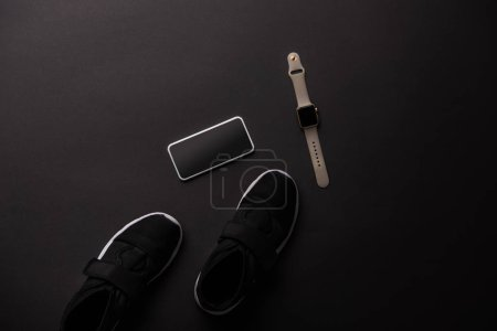 Photo for View from above of smartphone, smartwatch and sneakers isolated on black - Royalty Free Image