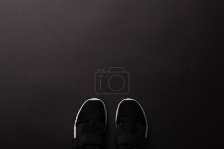 top view of sportive shoes isolated on black, minimalistic concept