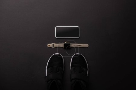 Photo for Flat lay with arranged smartphone, smartwatch and sneakers isolated on black, minimalistic concept - Royalty Free Image