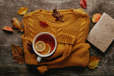 Photo for Flat lay with fallen leaves, cup of tea with lemon pieces, book and orange sweater on wooden tabletop - Royalty Free Image