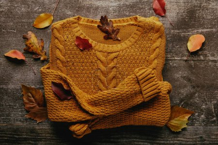 Photo for Flat lay with fallen leaves and orange sweater on wooden tabletop - Royalty Free Image