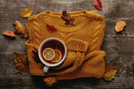 flat lay with fallen leaves, cup of tea with lemon pieces and orange sweater on wooden tabletop