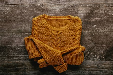top view of knitted woolen sweater on grey wooden tabletop