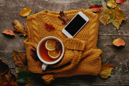 flat lay with cup of tea, ornage sweater, smartphone with blank screen and fallen leaves on wooden surface
