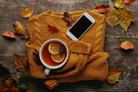 Photo pour Lay plat avec tasse de thé, ornage chandail, smartphone avec écran blanc et feuilles mortes sur la surface en bois - image libre de droit