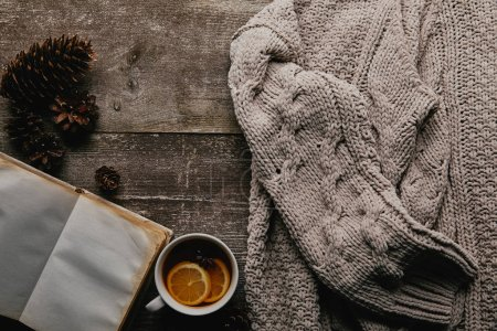 flat lay with woolen sweater, cup of tea and pine cones on wooden surface