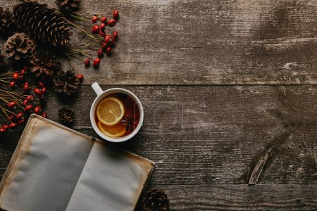 flat lay with red holly berries, blank notebook, cup of tea and pine cones on wooden tabletop
