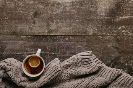 Photo for Flat lay with grey sweater and cup of tea with lemon pieces on wooden tabletop - Royalty Free Image