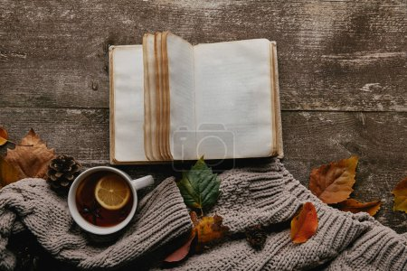 flat lay with grey sweater and cup of tea, blank notebook and fallen leaves on wooden tabletop