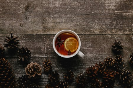 Photo for Top view of cup of hot tea and pine cones on wooden tabletop - Royalty Free Image