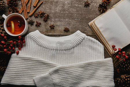 flat lay with white sweater, red holly berries, cinnamon sticks, blank notebook and cup of tea on wooden surface