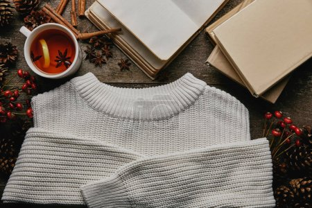 flat lay with white sweater, pine cones, cinnamon sticks, cup of tea and books on wooden surface