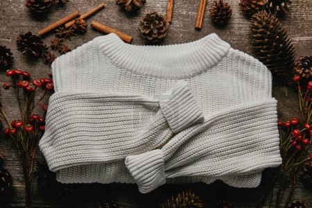 flat lay with white sweater, pine cones, cinnamon sticks and red holly berries on wooden surface