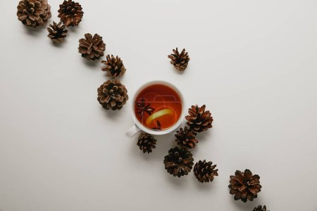 flat lay with pine cones and cup of hot tea on white backdrop