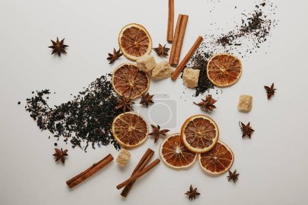 flat lay with arrangement of dried orange pieces, cinnamon sticks, anise stars and brown sugar on white backdrop
