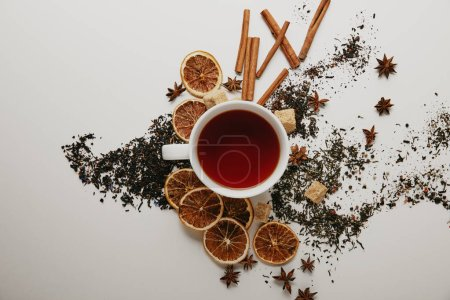 flat lay with arranged cinnamon sticks, anise stars, brown sugar, dried orange pieces and cup of hot tea on white background