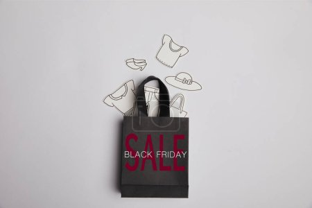 top view of black shopping bag with black friday sale inscription and paper clothes on grey background